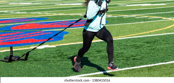 High school girl pulling a sled with twenty five pounds on it across a turf field wearing black spandex, ligh blue sweathshirt and gloves.