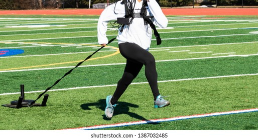 A high school girl is pulling a sled with weight during a clod day wearing a white sweatshirt and black spandex.
