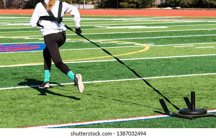 A high school girl is running away from the camera pulling a sled with weight across a green field wearing black spandex and gray sweatshirt.