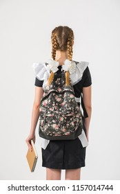 A high school girl student in school uniform with a backpack and a notebook. beautiful teenagers in dress back to school on white background. Child boy with bag go to elementary school.