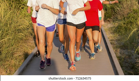 A high school girls cross country team running as a group on the boardwalk  from the 828006053739