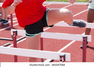 High school girls doing hurdle drills, working on her trail leg, at track and field practice