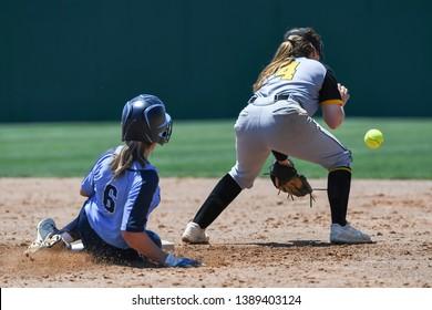 High School Girls making plays during a softball game