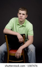 High school guy sitting in a chair backwards.  In heavy thought or maybe a bit sad looking.  Shot in studio.