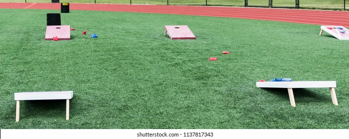A high school gym class has wooden corn hole games set up on its turf field with bean bags for classes.