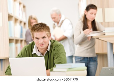 High school library - Student with book and laptop