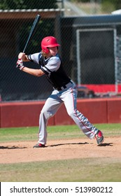 High school player swinging the bat during a game.
