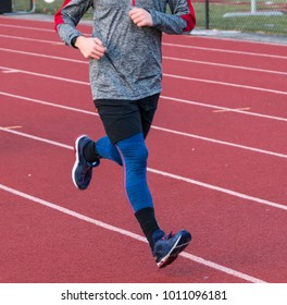 A high school runner is running on a track with long sleeve and blue spandex on a cool afternoon after school.