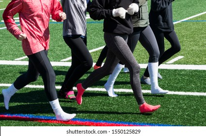 A high school running team is running together wearing spandex and socks with long sleeves due to cold weather.