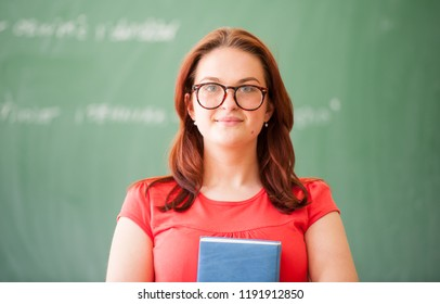 High school student standing infront of chalk board