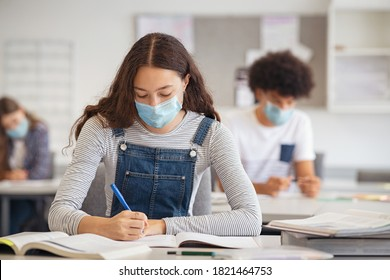 High school student taking notes while wearing face mask due to coronavirus emergency. Young woman sitting in class with their classmates and wearing surgical mask due to Covid-19 pandemic.
