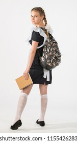 A high school student in school uniform with a backpack and a notebook. the girl is ready to go to school. beautiful teenagers in festive dress back to school on white background. the beginning.