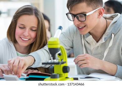 High School students. Girl and boy working together at biology classroom: choosing a biological sample on glass to look through microscope