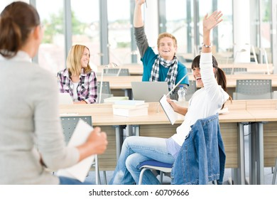 High school students raising hands, in classroom with professor