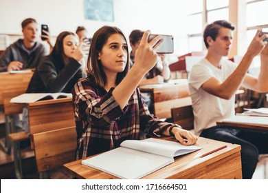 High school students recording the lecture in classroom. Group of boys and girls filming the lecture by a teacher in classroom with their cell phones.