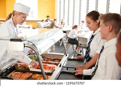 High School Students Wearing Uniform Being Served Food In Canteen