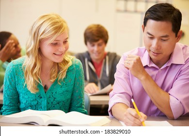 High School Teacher Helping Student With Written Work