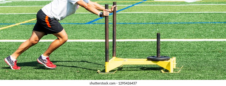 A high school teenage boy is pushing a yellow sled that has a 25 pound wieght on it during strength and conditioning practice.