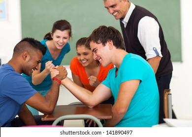 high school teenage boys arm wrestling in classroom