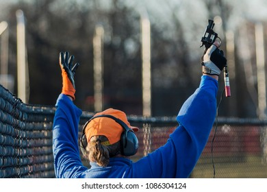 A high school track and field official raises his pistol in the air to start a race.