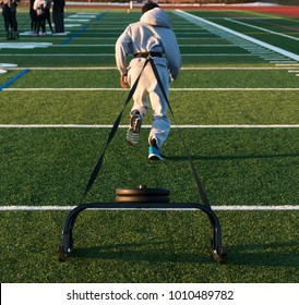A high school track and field sprinter is pulling a sled with 50 pounds of weights on it across a green turf field for strength and speed work on a cool winter afternoon.