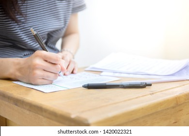 high school or university student holding pencil writing on paper answer sheet.sitting on lecture chair taking final exam attending in examination room or classroom.scholarship for study abroad