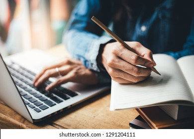 high school,college,university student using typing laptop searching information from network.people writing on notebook in modern library concept for scholarship to research international education l