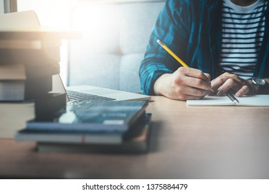 high school,college,university student writing in class room or library at work space with book stack for knowledge prepare exams scholarship study abroad.research world international education learn