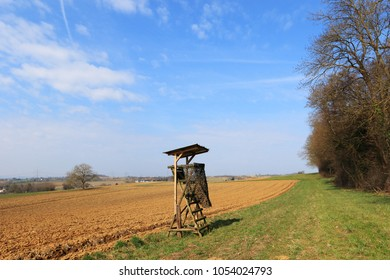 High seat against wild boar infestation. View of open high seat at the edge of the forest. View of open farmland. Blue sky, veil clouds. Spring timen farmland.