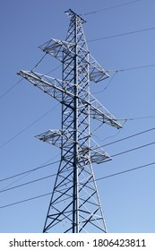 High single electric power mast of an air power line closeup, new electricity pylon with wires and insulators on clear blue sky background, traditional energy net