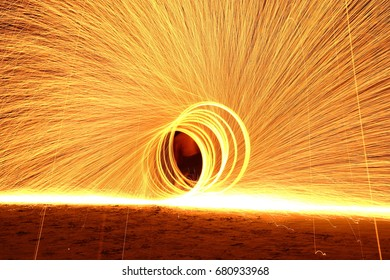 High Skill Man playing fireworks by spinning wood pole with fuel oil and fire, circle around as ring of fire on beach along ocean in tropical island, long high exposure blur movement