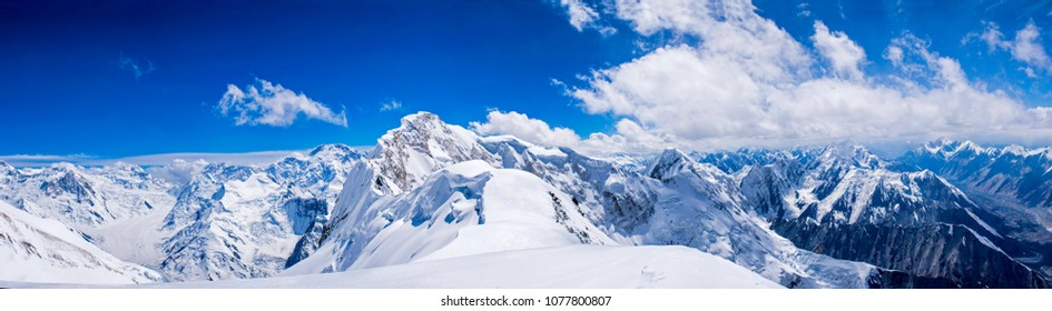 High snow mountains in Central Asia with big rock walls and glaciers under the clouds in a cold summer day.