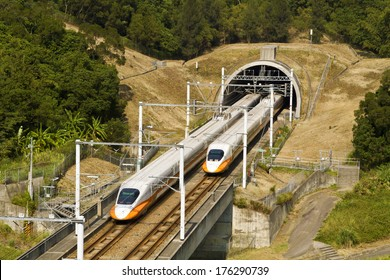 high speed commuter train driving across tunnel with mountain scenery