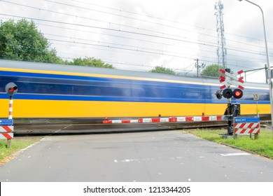High speed dutch passenger train passing at railroad crossing in The Netherlands