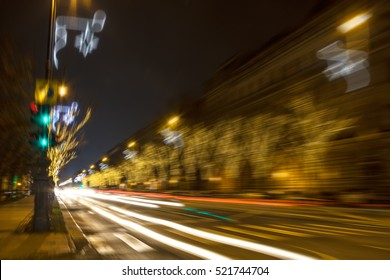 High speed festive night drive - motion blurred image of winter city road with bordering decorated trees and lamp-posts for Christmas