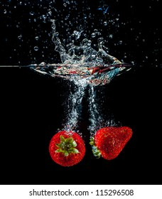 High speed freeze action shot of strawberries splashing into water with a black background