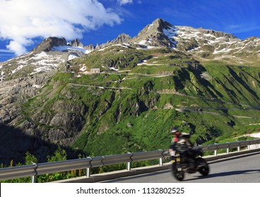 High speed motorcycle passing on Furka Pass road in Switzerland Alps, Europe