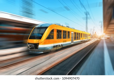 High speed orange train in motion on the railway station at bright day. Modern intercity train with motion blur effect on the railway platform. Industrial. Passenger commuter train on railroad. Travel