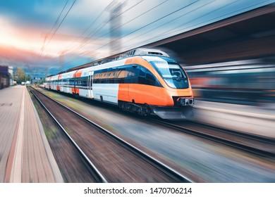 Hochgeschwindigkeitszug Orange in Bewegung auf dem Bahnhof bei Sonnenuntergang. Moderner Intercity-Personenzug mit Bewegungsunschärfe auf dem Bahnsteig. Industriell. Eisenbahn in Europa. Verkehr