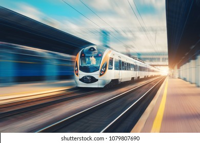 High speed passenger train in motion on the railway station at sunset in Europe. Modern intercity train on railway platform with motion blur effect. Urban scene with railroad. Railway transportation