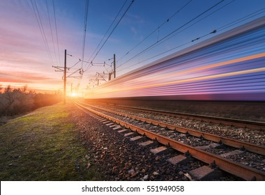 High speed passenger train in motion on railroad at sunset. Blurred commuter train. Railway station against sunny sky. Railroad travel, railway tourism. Rural industrial landscape. Concept