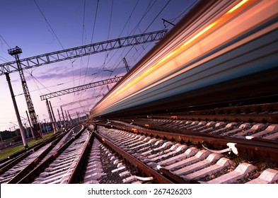 High speed passenger train on tracks with motion blur effect at sunset. Railway station in Ukraine