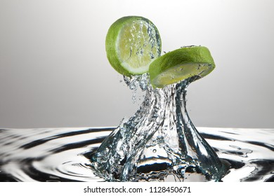 High speed photograph of fresh lime slices splashing through water.