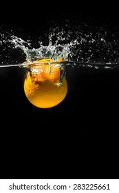 High speed photography of fruits & vegetables with splash in water isolated on black background - ORANGE