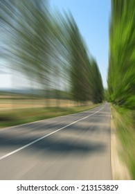 High speed road travelling - motion blurred image of summer road with bordering trees
