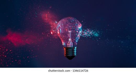 Hochgeschwindigkeits-Studiofotografie, Augenblick der Wirkung einer Kugel auf eine klassische elektrische Glühbirne. Detail der Glasexplosion, blaue und violette Beleuchtung. Konzept der veralteten Energie.