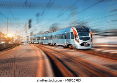 High speed train arrives on the railway station at sunset. Modern intercity train in motion on the railway platform. Passenger train on railroad with motion blur effect. Railway transportation