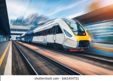 Hochgeschwindigkeitszug in Bewegung auf dem Bahnhof bei Sonnenuntergang. Moderner Intercity-Personenzug mit Bewegungsunschärfe auf dem Bahnsteig. Industriell. Eisenbahn in Europa. Gewerblicher Transport