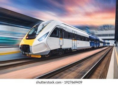 High speed train in motion on the railway station at sunset. Modern intercity passenger train with motion blur effect on the railway platform. Industrial. Railroad transportation in Europe