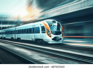 High speed train in motion at the railway station at sunset in Europe. Modern intercity train on the railway platform with motion blur effect. Industrial landscape with passenger train on railroad